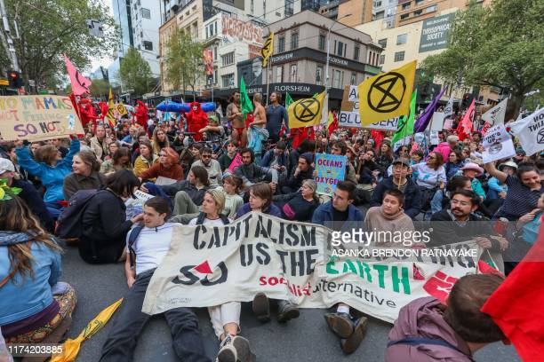 Demonstrators stage a sitin on a road during a Extinction Rebellion protest in Melbourne on October 7 2019 Extinction Rebellion activists began...