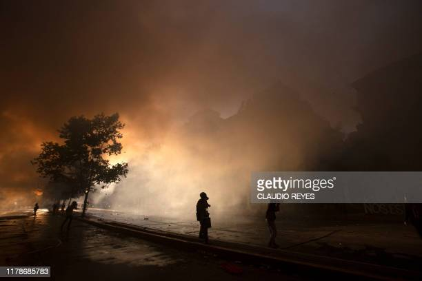 Demonstrators stand amid smoke during clashes with riot police outside La Moneda presidential palace in Santiago on October 28 2019 Chilean President...