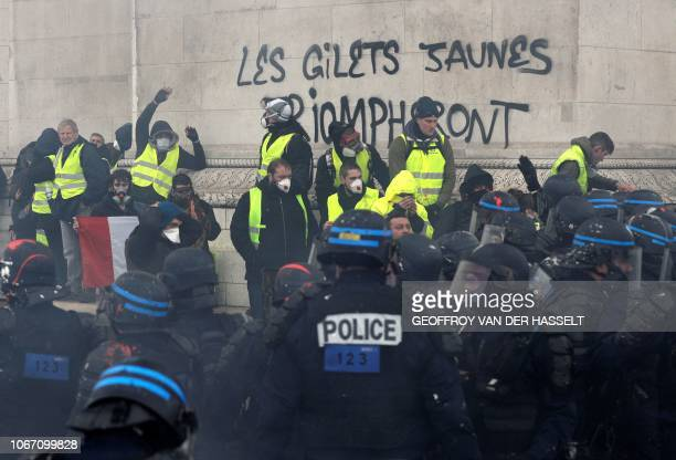 TOPSHOT Demonstrators stand at the Arc of Triomphe after writing on a wall of the monument Yellow wests will triumph as they clash with riot police...