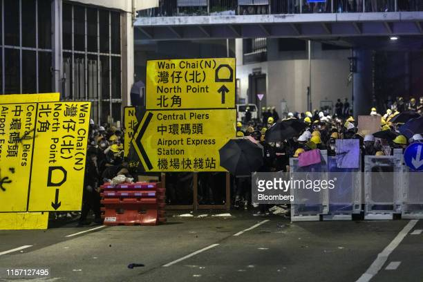 Demonstrators stand behind road signs and shields as they stand off against riot police during a protest in the Sheung Wan district of Hong Kong...
