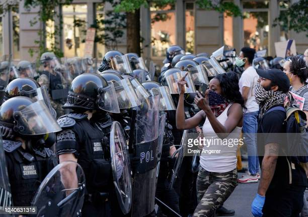 Demonstrators stand in front law enforcement who are holding a perimeter during protest on June 1 2020 in downtown Washington DC Protests and riots...