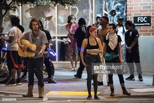 Demonstrators stand in front of a damaged store front September 22 2016 in downtown Charlotte NC The North Carolina governor has declared a state of...