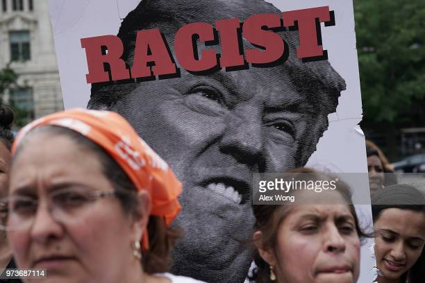 Demonstrators stand in front of a poster of US President Donald Trump during a protest June 13 2018 in Washington DC Democratic congressional members...