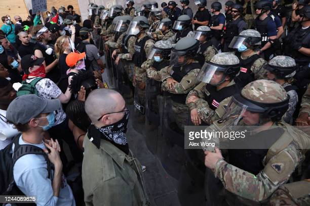 Demonstrators stand in front of D.C. National Guard and other law law enforcement officers during a peaceful protest against police brutality and the...