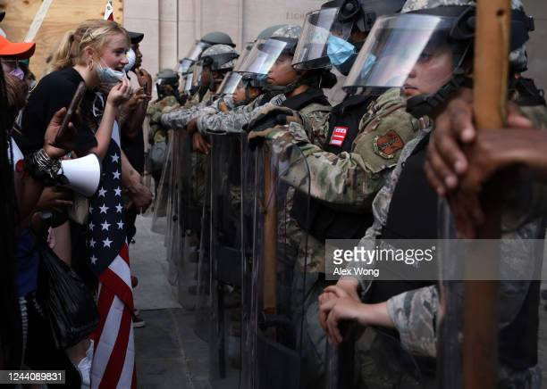 Demonstrators stand in front of DC National Guard and other law law enforcement officers during a peaceful protest against police brutality and the...