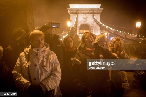 Demonstrators stand in front of police on Budapest's famous Szechenyi Chain Bridge after police blocked them from leaving after attending a...