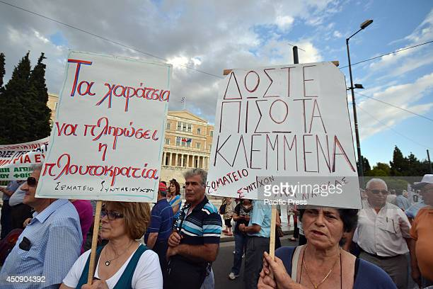 Demonstrators stand in front of the Greek Parliament buildings at Syntagma Square, Athens, whilst holding placards with messages of anger directed...