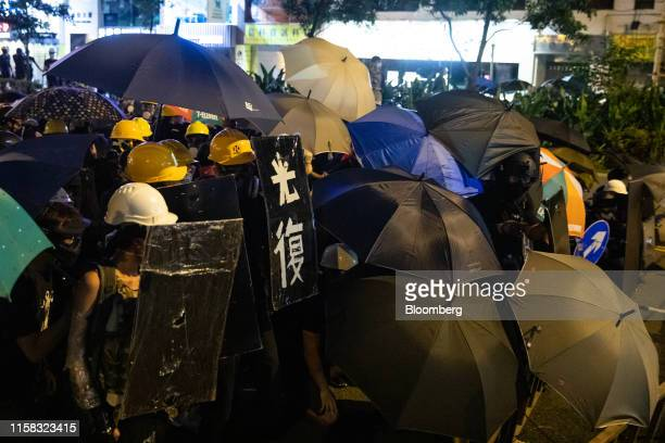 Demonstrators stand off against riot police during a protest in Sheung Wan district of Hong Kong, China, on Sunday, July 28, 2019. From an airport...