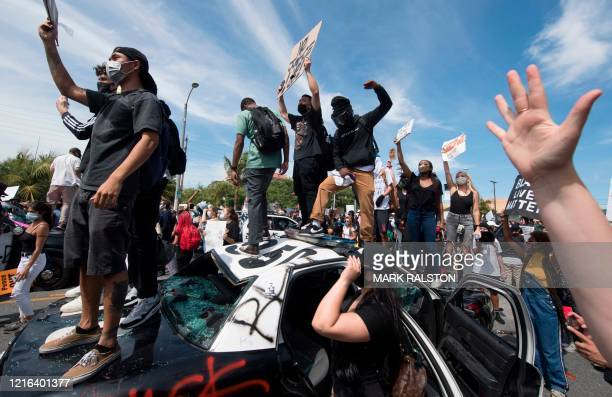 Demonstrators stand on a smashed police vehicle in the Fairfax District as they protest the death of George Floyd, in Los Angeles, California on May...