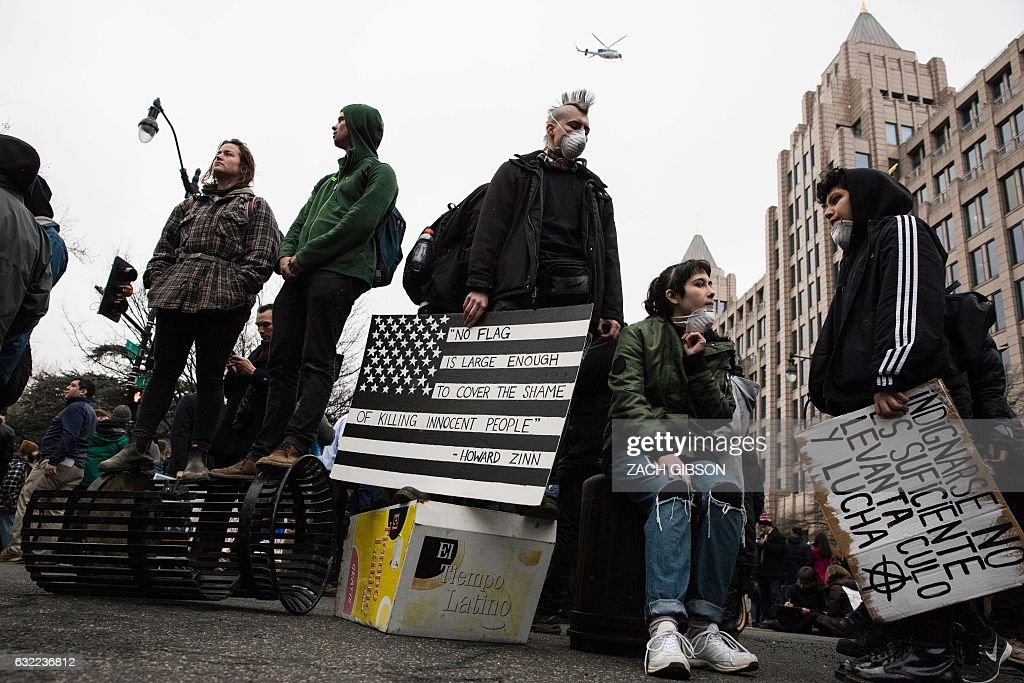 TOPSHOT - Demonstrators stand on overturned trash cans and newspaper stands during a protest reacting to the inauguration of US President Donald Trump on January 20, 2017 in Washington, DC. / AFP / ZACH