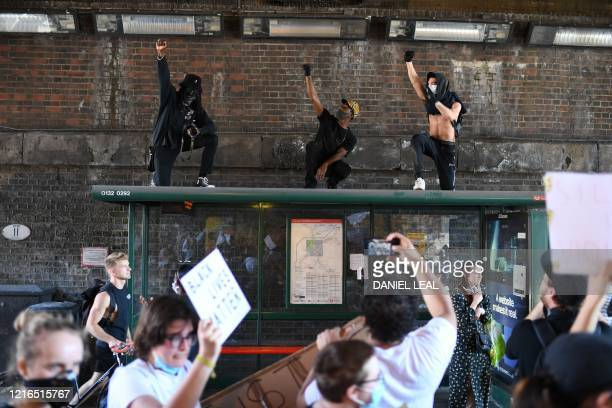 Demonstrators stand on top of a bus shelter they march near the US Embassy in central London on May 31, 2020 to protest the death of George Floyd, an...