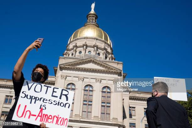 Demonstrators stand outside of the Capitol building in opposition to House Bill 531 on March 8, 2021 in Atlanta, Georgia. HB531 will restrict early...