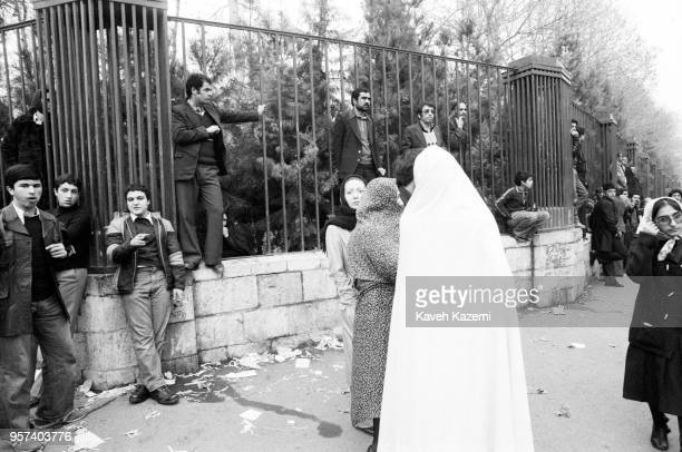 Demonstrators stand outside the Tehran University by the iron fence during the protests on Ashura Day in Shah Reza street during the Iranian...