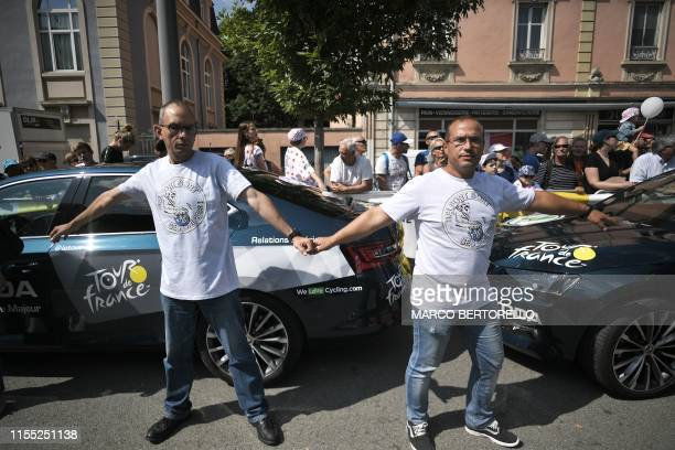 Demonstrators stand past Tour de France organization vehicles during a demonstration held to support the employees of US giant General Electric...
