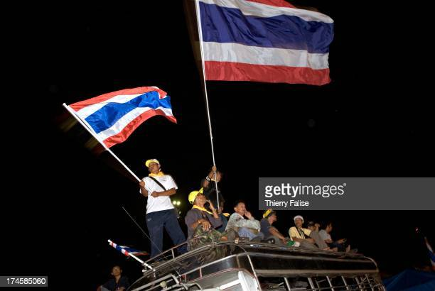 Demonstrators standing on the top of a bus wave Thailand national flag Thousands of demonstrators have defied warnings of a crackdown from the Thai...