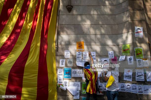 Demonstrators stick posters on a wall during a Catalan ProIndependence meeting on September 24 2017 in Barcelona Spain Spain's government announced...