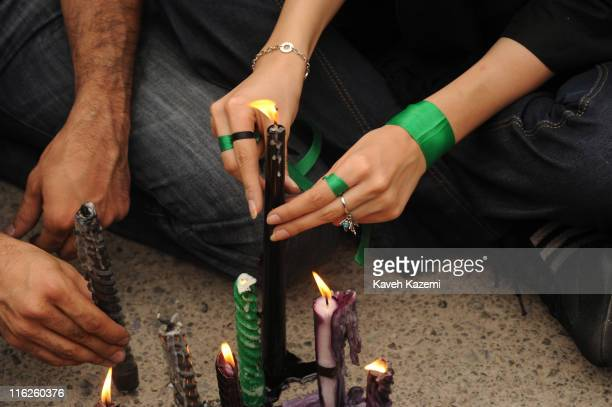 Demonstrators supporters of the Green Movement wear green ribbons around their wrists whilst holding a vigil on Imam Khomeini Square in Tehran for a...