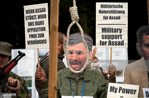 Demonstrators symbolically hang Iranian President Mahmoud Ahmadinejad during a rally of opponents to the governments of Syria and Iran on August 16...