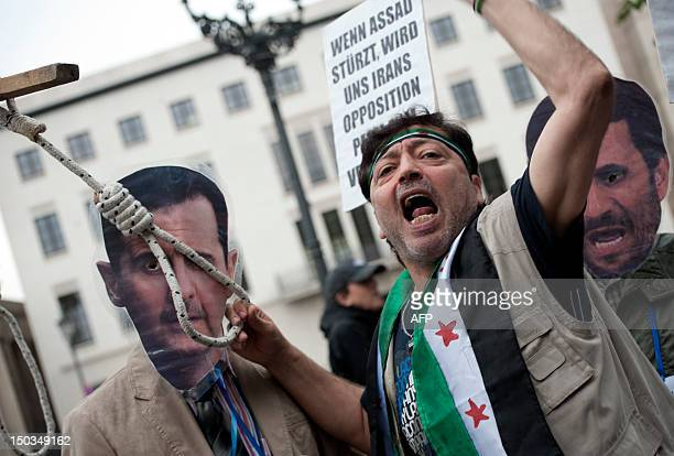 Demonstrators symbolically hang Syria's President Bashar alAssad and Iranian President Mahmoud Ahmadinejad during a rally of opponents to the...