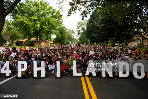 Demonstrators take a knee and hold up a fist as they march in honor of Philando Castile on July 6, 2020 in St. Anthony, Minnesota. Philando Castile...