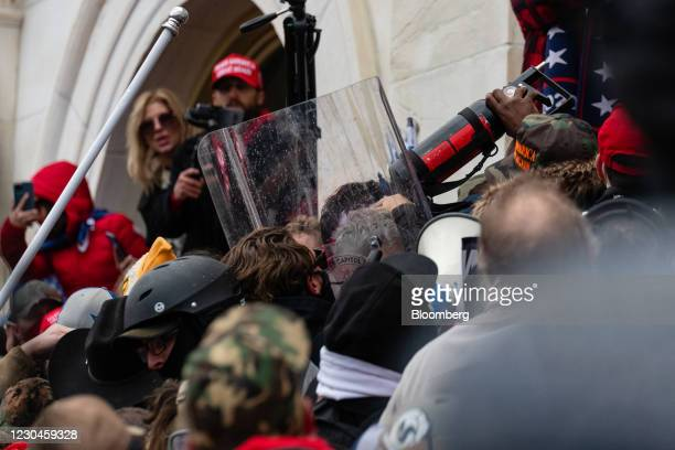 Demonstrators take a Metropolitan Police department riot shield and pepper spray canister from law enforcement in an attempt to enter the U.S....