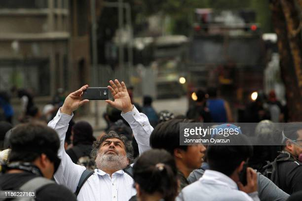 A demonstrators take a selfie during protests against president Piñera at Plaza Italia on December 2 2019 in Santiago Chile To reduce social unrest...