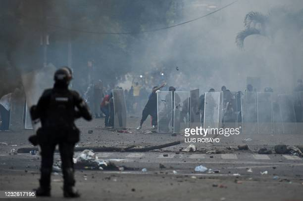 Demonstrators take cover behind makeshift shields during clashes with riot police officers following a protest against a tax reform bill launched by...