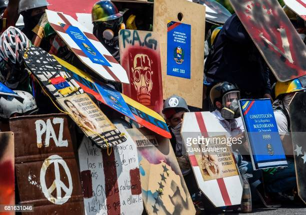 Demonstrators take cover behind their shields as they clash with riot police during a protest against President Nicolas Maduro in Caracas on May 10...