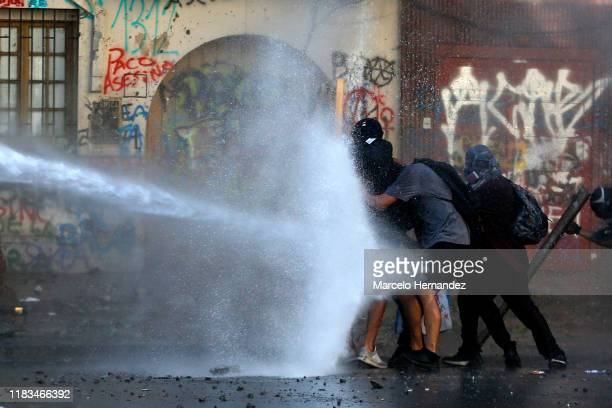 Demonstrators take cover from water fired by a riot police truck during a protest against President Sebastian Piñera on November 19 2019 in Santiago...