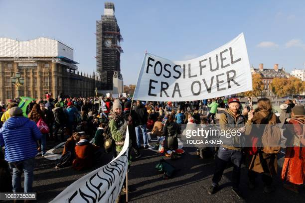 Demonstrators take part in a proenvironment protest as they block Westminster Bridge near the Houses of Parliament in central London on November 17...