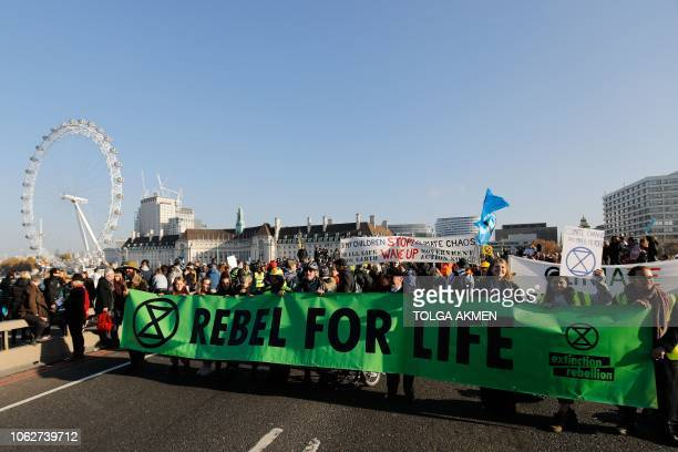 Demonstrators take part in a pro-environment protest as they block Westminster Bridge in central London on November 17 calling on the British...