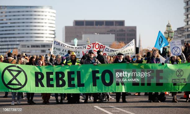 Demonstrators take part in a proenvironment protest as they block Westminster Bridge in central London on November 17 calling on the British...
