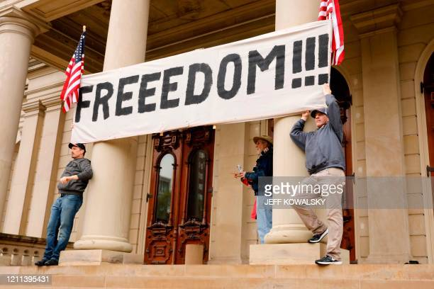 TOPSHOT Demonstrators take part in an American Patriot Rally organized on April 30 by Michigan United for Liberty on the steps of the Michigan State...