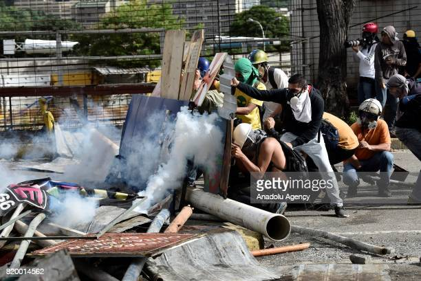 Demonstrators take shelter behind a barricade of debris during clashes with the Bolivarian National Guard in an antigovernment protest in Caracas on...