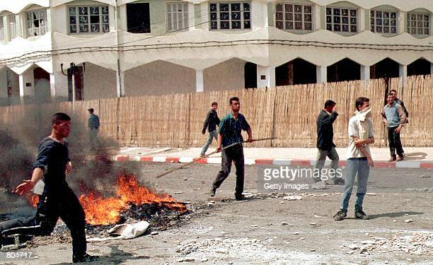 Demonstrators take up positions near a fire burning on a street during riots April 26 2001 in the Berber capital of Tizi Ouzou Algeria 62 miles east...