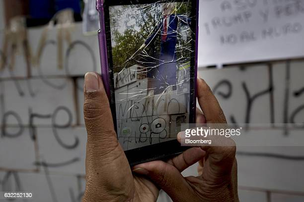 A demonstrators takes a photograph of an effigy of US President Donald Trump using a smartphone with a shattered screen in front of the US embassy...