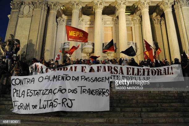 Demonstrators takes part in a protest against a public transport fare hike announced for January 2014 by Rio de Janeiro's Mayor Eduardo Paes, outside...