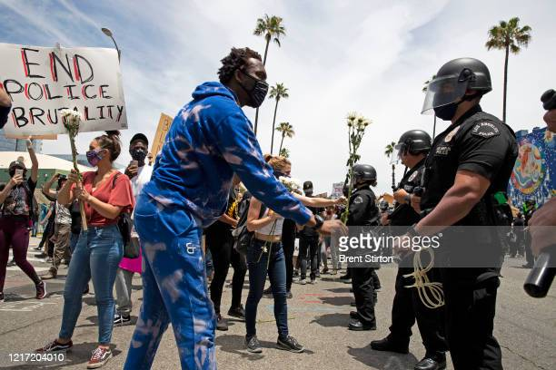 Demonstrators talk to members of the LAPD during a march in response to George Floyd's death on June 2, 2020 in Los Angeles, California. Floyd died...