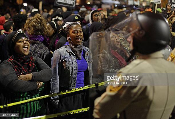Demonstrators taunt police officers in riot gear as they protest the shooting death of Michael Brown outside the Ferguson Police Station October 11...