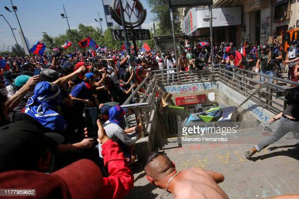 Demonstrators through a phonebooth against a closed subway entrance during the seventh day of protests against President Sebastian Piñera on October...