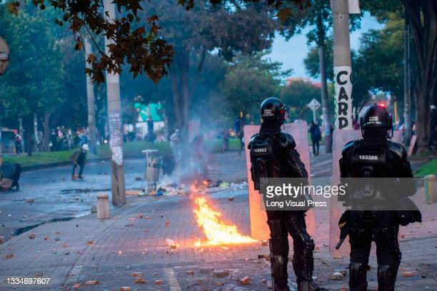 Demonstrators throw a molotov bomb near Colombia's riot police officers during anti-government that ended in clashes between protesters and...
