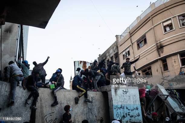 Demonstrators throw dozens of stones over a barricade near Ahrar Bridge where there have been recent clashes between demonstrators and Iraq security...