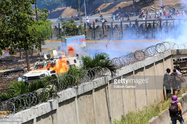 Demonstrators throw petrol bombs to military forces at the air force base La Carlota on April 30 2019 in Caracas Venezuela Through a live broadcast...