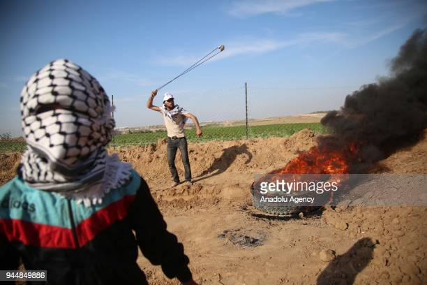 Demonstrators throw rocks with slingshots and burn tires in response to Israeli soldiers' intervention to remark the 'Great March of Return' at the...