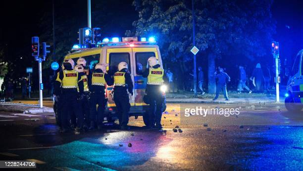 Demonstrators throw stones at police during clashes in the Rosengard neighbourhood of Malmo, Sweden, on August 28, 2020. - The protest was sparked by...