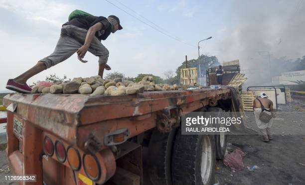 TOPSHOT Demonstrators throw stones in clashes with the security forces at the Francisco de Paula Santander international bridge Bridge linking Cucuta...