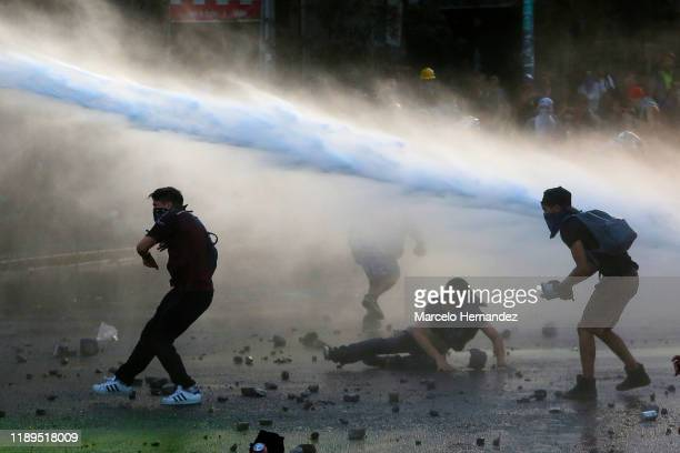 Demonstrators throw stones to riot police as they are being sprayed with cannon water during a protest against the government of President Sebastian...