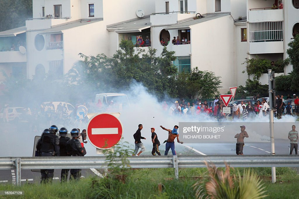 Demonstrators throw stones to riot police in the city of Le port, west of the French island of La Reunion, on February 18, 2013, as they were demonstrating since the morning to demand government-subsidized contracts. The demonstrators blocked in the morning the main road between the north and the south of the island but after one hour of riot later in the day, the traffic start again without any injuries.