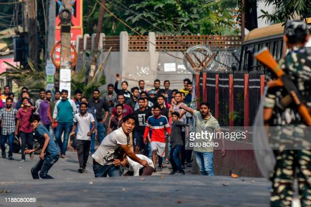 Demonstrators throw stones to security personnel during a protest against the government's Citizenship Amendment Bill in Guwahati on December 12,...