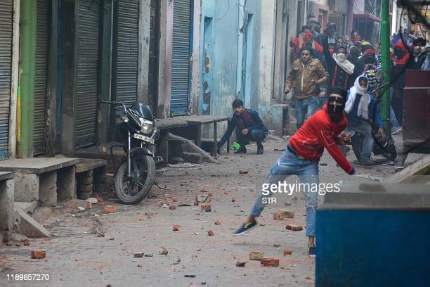 Demonstrators throw stones to security personnel during demonstrations against India's new citizenship law in Meerut on December 20, 2019. - Five...